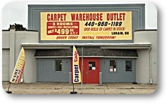 outside view of carpet warehouse sign sits overtop of two entrance doors that reads Carpet Warehouse Outlet